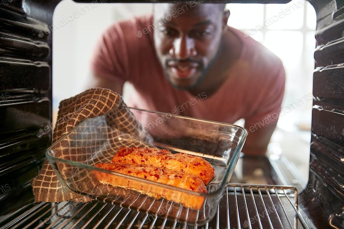 View Looking Out From Inside Oven As Man Cooks Oven Baked Salmon