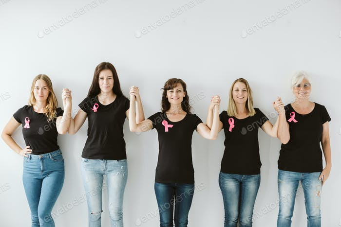 Five women in black tshirts and blue jeans standing together