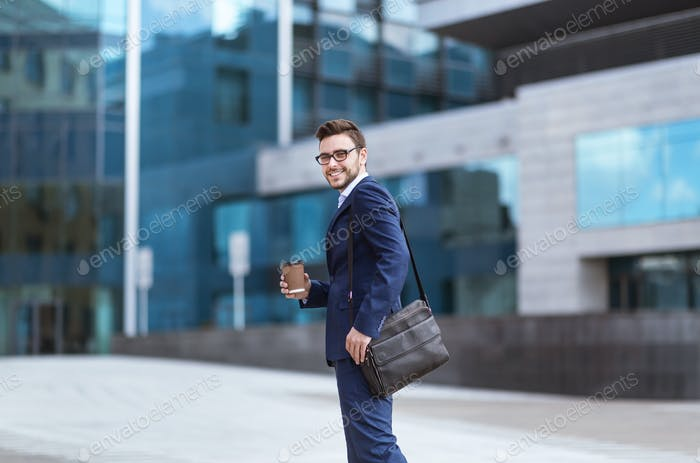 Handsome businessman with takeaway coffee going to his office building in morning