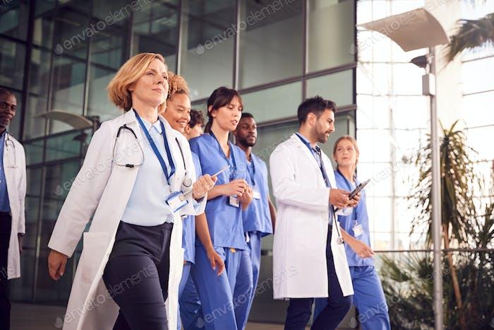 Medical Team Walking Through Lobby Of Modern Hospital Building