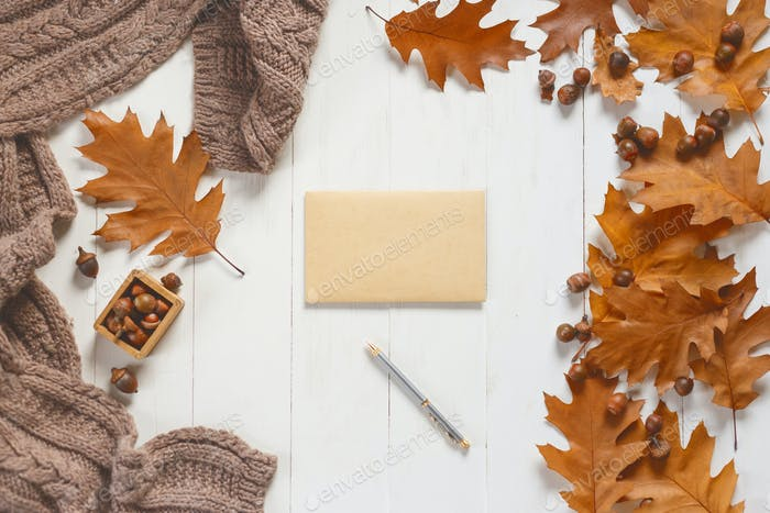 Unsigned envelope and pen on white wooden table with autumn accessories. View from above
