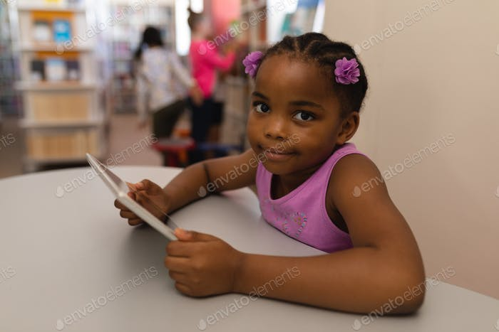 Schoolgirl with digital tablet looking at camera on table in school library