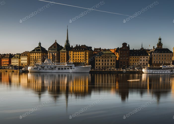 Boats at harbor in Gamla stan against clear sky