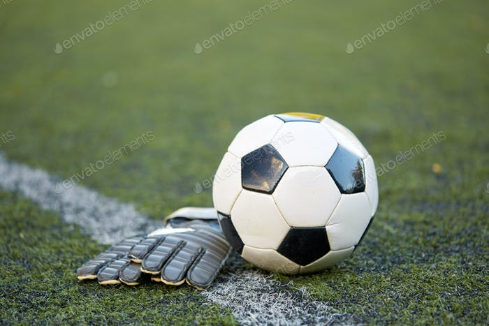 soccer ball and goalkeeper gloves on field