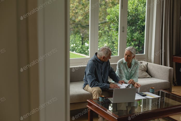 Side view of active senior Caucasian couple calculating bills in living room at home