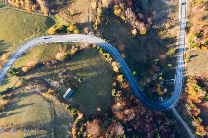 Curvy road in autumn forest.