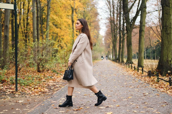 Side view of attractive brunette girl in coat walking around beautiful autumn park