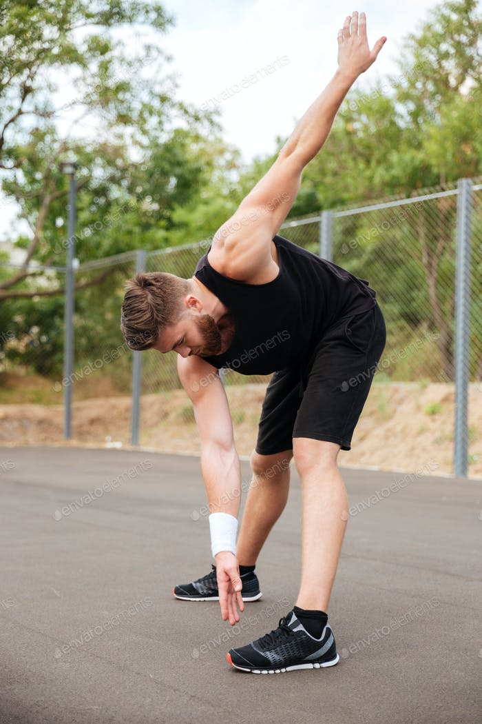 Portrait of athletic bearded man doing stretching exercises