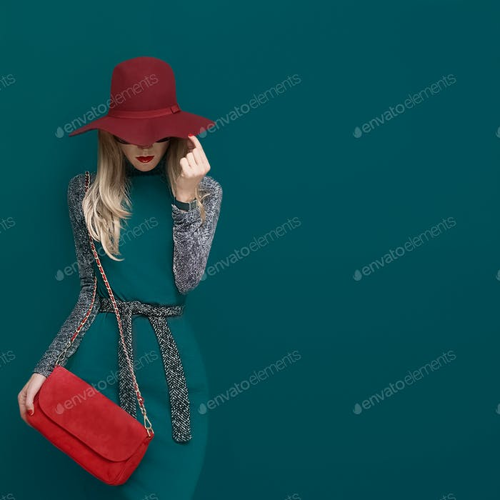 Schönes blondes Modell in modischen roten Hut und eine rote Clutch auf gr