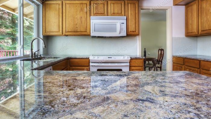 55289,Granite counter reflecting kitchen cabinets