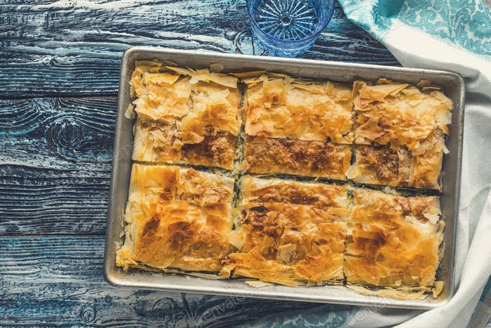 Greek pie spanakopita in the metal pan  on the blue wooden table top view
