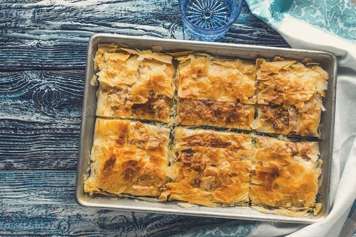 Griechische Kuchen spanakopita in der Metallpfanne auf dem blauen Holztisch oben Ansicht