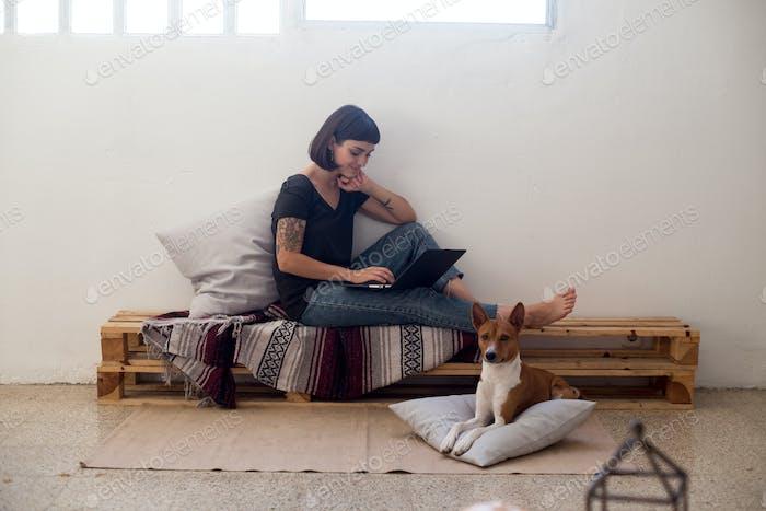 Mujer linda en el acogedor espacio de coworking con el perro