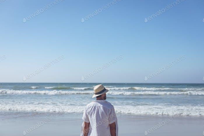 Young man standing face to the ocean at beach on sunny day