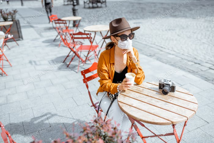 Woman in facial protective mask at the cafe outdoors