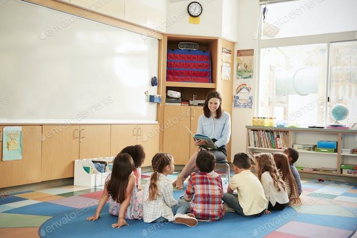 School kids sitting on the floor gathered around teacher
