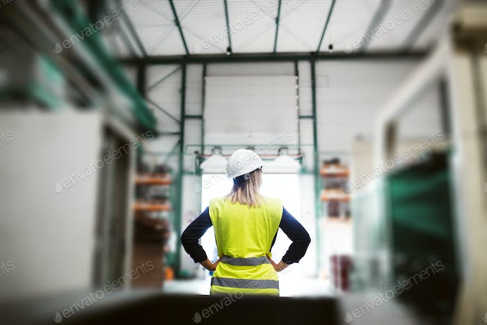 A rear view of an industrial woman engineer standing in a factory, arms on hips.