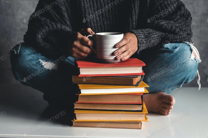 Stack of books with mug on top in front of woman reading book, education, training, hobbies