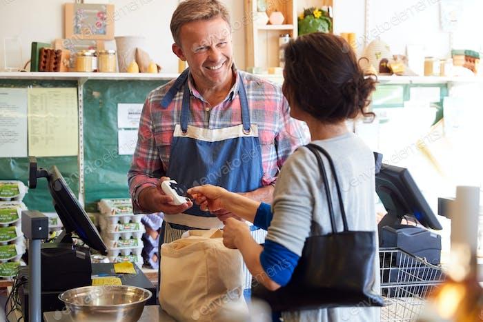Kunde an der Kasse von Bio-Bauernhof Shop machen kontaktlose Zahlung