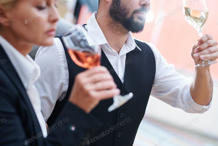 Bearded sommelier with glass of white wine checking its quality