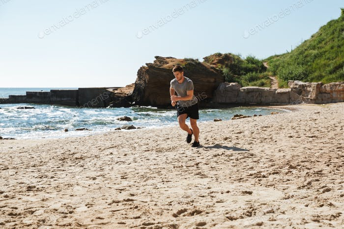 Healthy young sportsman jogging on a sand