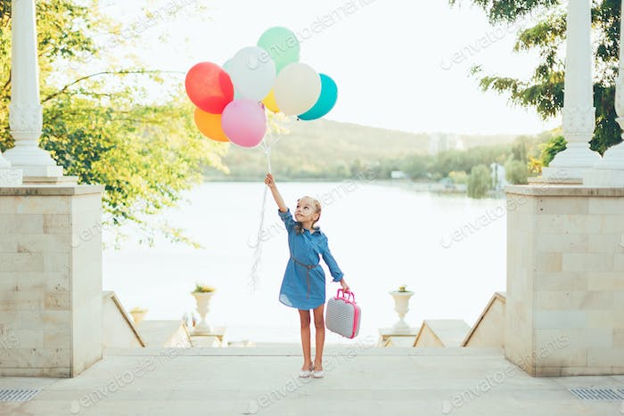 Cheerful girl holding colorful balloons and childish suitcase