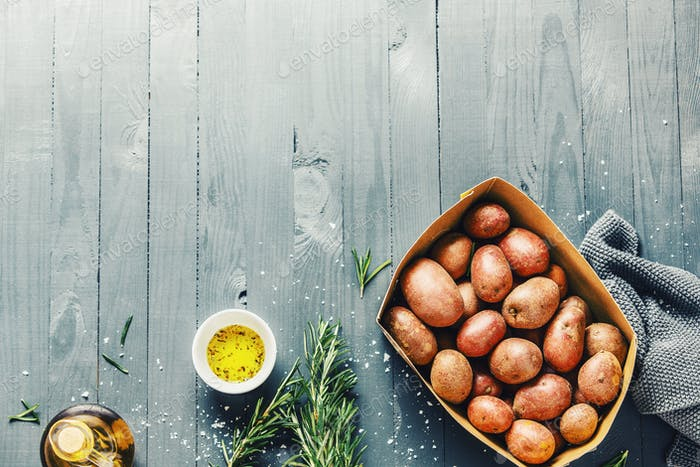 Raw organic potatoes with spices on wooden table