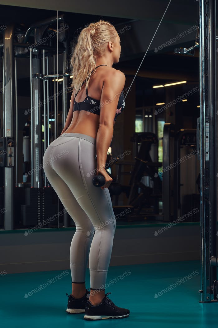 Athletic blonde woman in sportswear doing exercise on the triceps on the crossover machine in a gym.