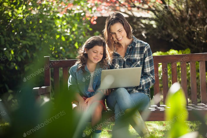 Smiling mother and daughter using laptop while sitting on wooden bench