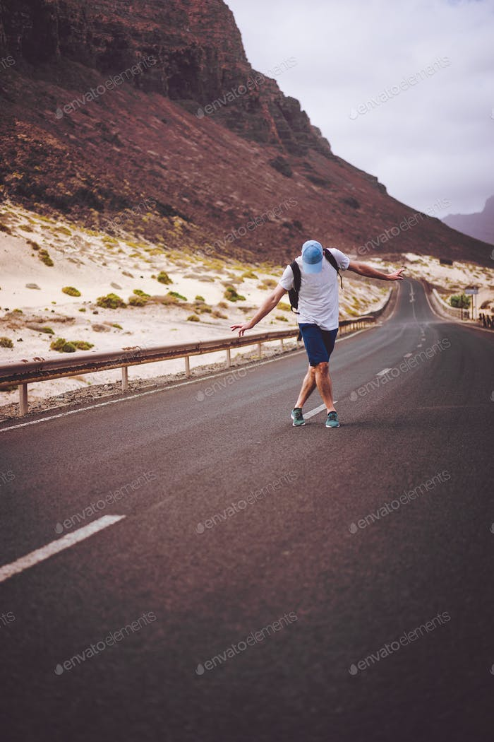 Traveler with backpack standing in the center of an epic winding road. Huge volcanic mountains in