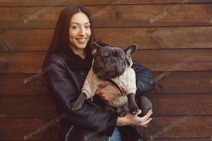 Elegant woman in a black jacket with black bulldog
