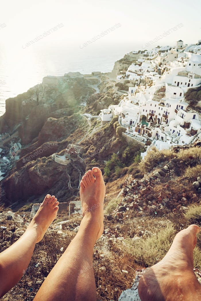 Oia village seen from two people with legs visible in the photo.