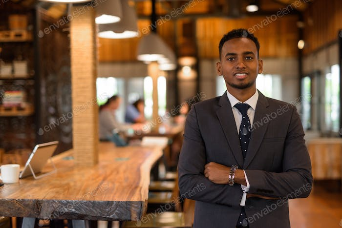 Happy young African businessman with arms crossed smiling