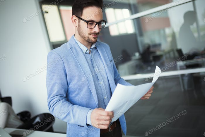 Architect holding project plans and blueprints in office