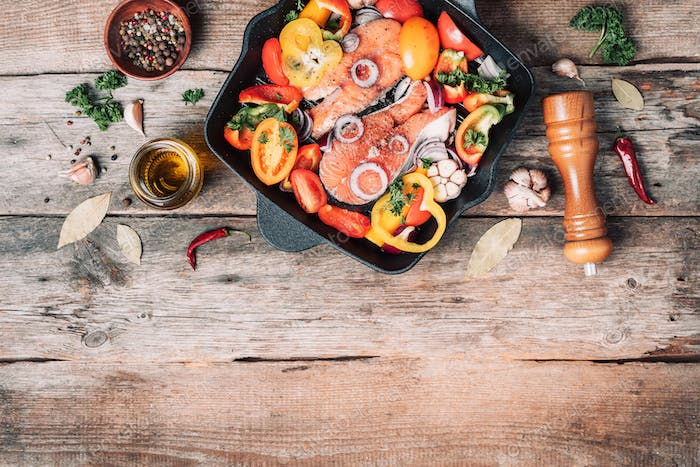 Raw uncooked salmon fish with vegetables, herbs, spices in iron grilling pan over wooden background