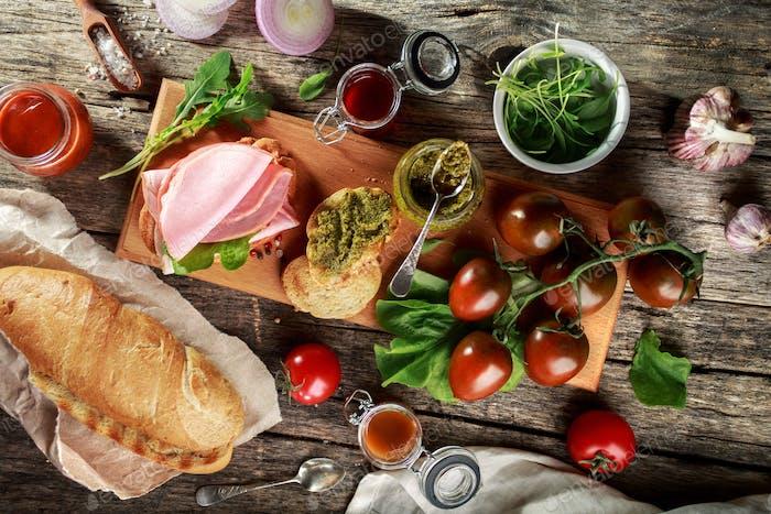 Baguette, Schinken und Gemüse. Vorspeisen auf Holzschneidebrett.