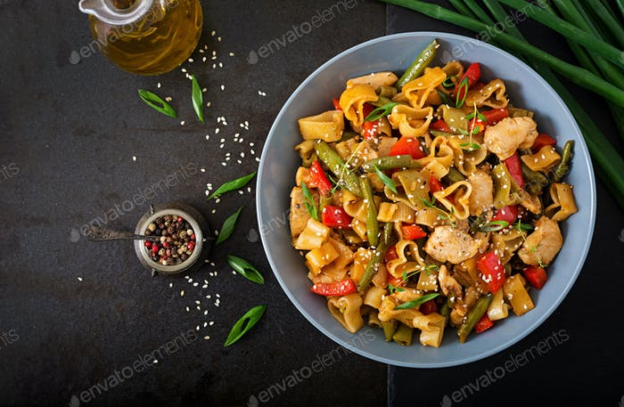 Stir Fry from chicken fillet, green beans and paprika with pasta in the form of heart.