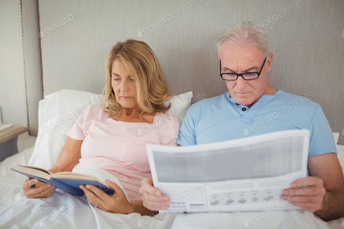 Senior couple on bed reading newspaper and book