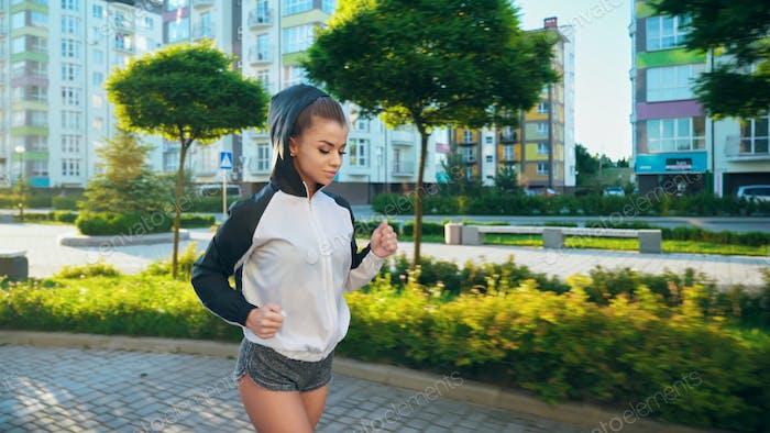 Sportlerin läuft in der Morgenstadt