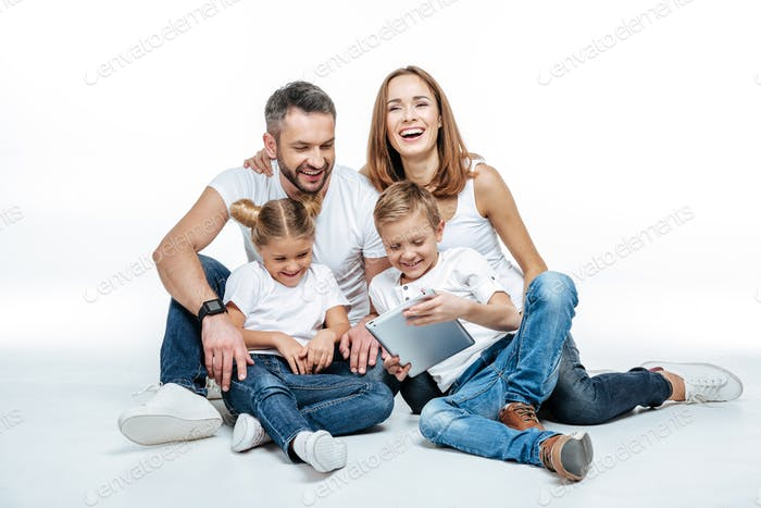 Smiling family in white t-shirts and jeans sitting together and using digital tablet isolated on