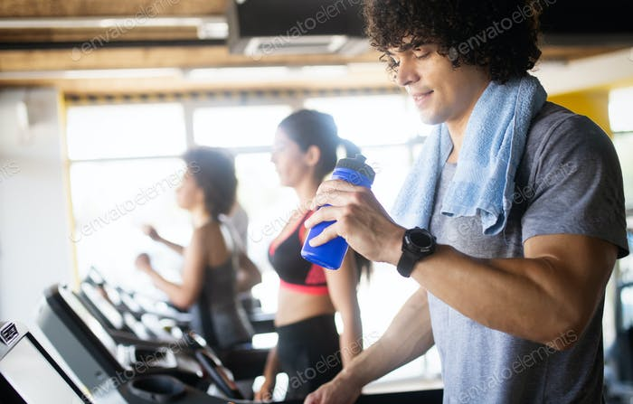 Beautiful fit people exercising together in gym