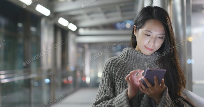 Woman using cellphone in city at night