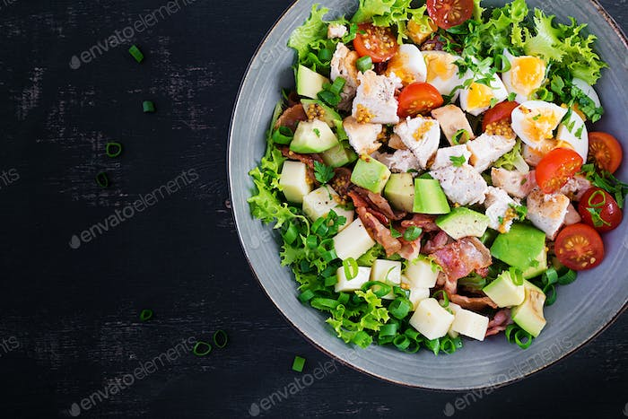 Healthy cobb salad with chicken, avocado, bacon, tomato, cheese and eggs.