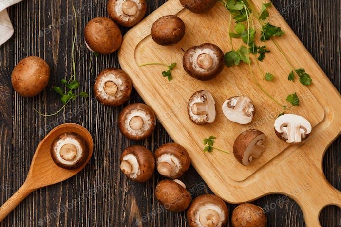 Schneidebrett mit geschnittenen Pilzen, Messer und Serviette auf einem braunen Sackleinen Holzhintergrund. Draufsicht.