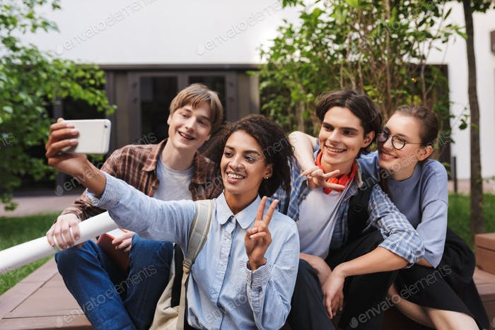 Group of young smiling students sitting and taking cute photos on cellphone