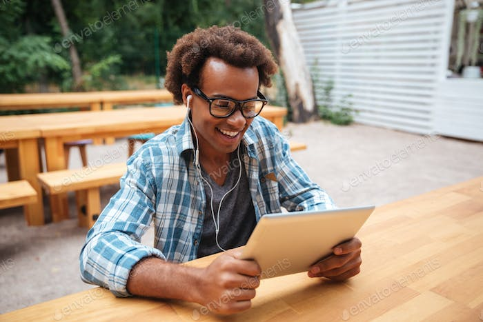 Smiling african man sitting and using tablet in outdoor cafe