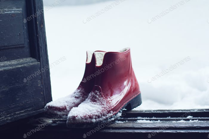 red rubber shoes covered in snow by the door