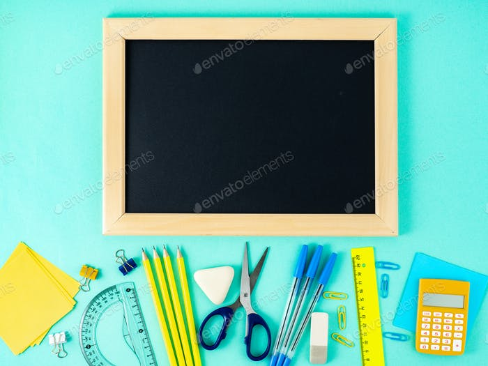 Chalkboard and school supplies on white table by the blue wall