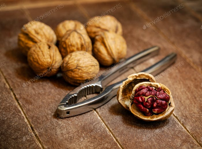 Red Danube Walnuts with silver nutcracker on wooden background