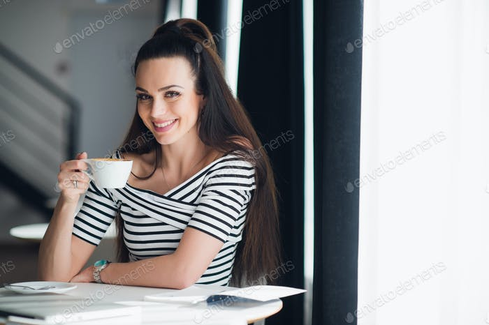 Portrait of beautiful young woman sitting at a table with a cup of coffee in hand looking at camera